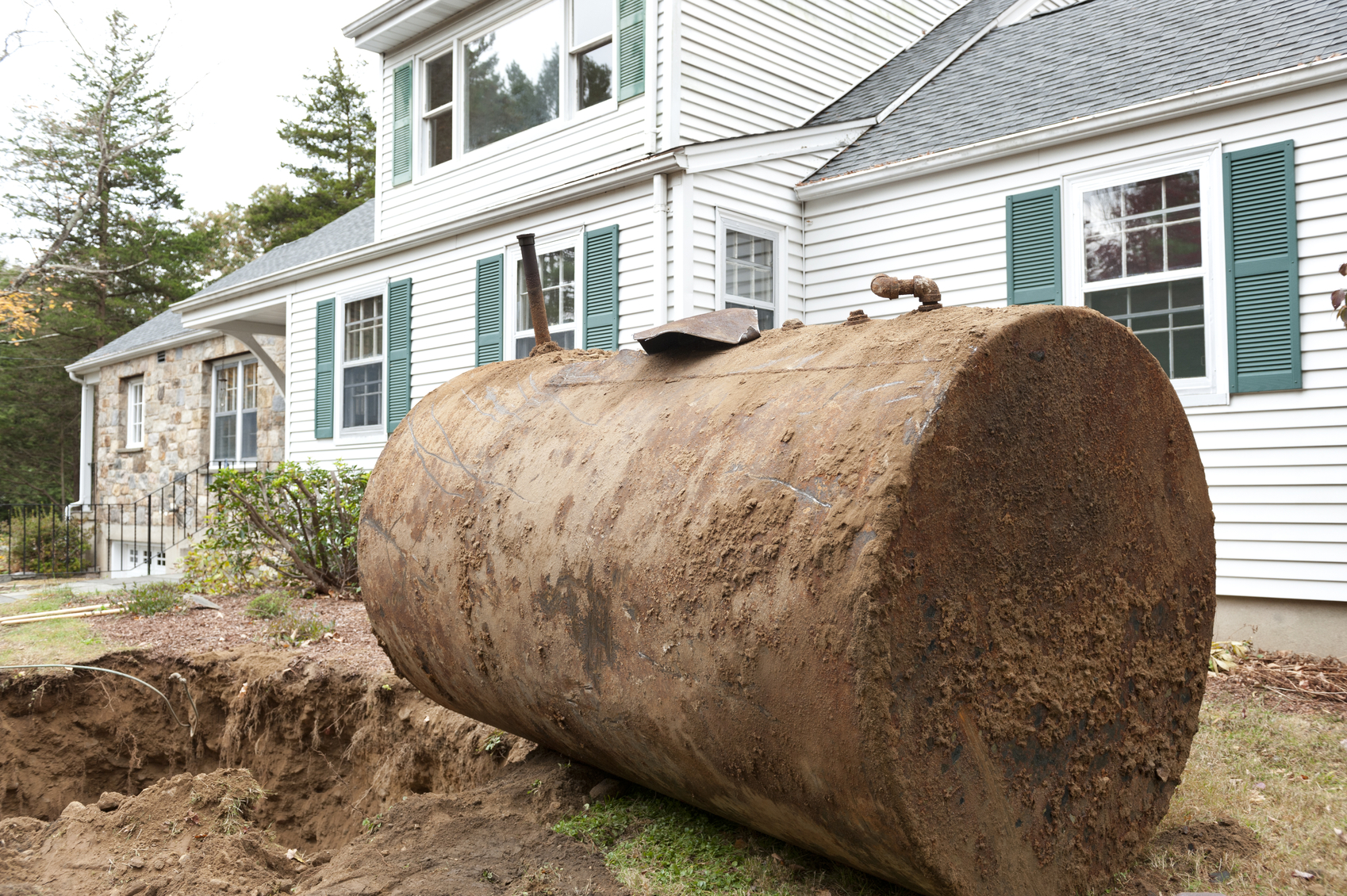An old rusty underground oil tank in front of a residential house.